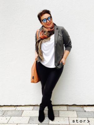 Plus Size Mode cool kombinieren: smarter grauer Blazer, weiße Bluse und eine Hose mit glänzender Oberfläche geben einen modernen Look.