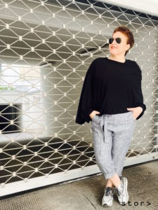 Coole Plus Size Fashion von stor> in Wien Josefstadt. Hier zeigt die stor> Inhaberin eine lässige Paperbag-Leinenhose und einen schwarzen Jerseyponcho.